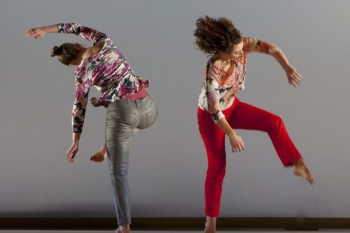 two dancers bend and reach away from each other