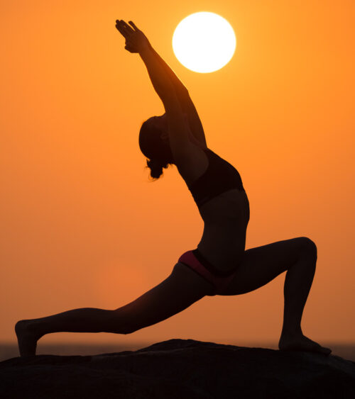 A yoga pose with the sun in the distance