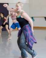 Abby reaches her right arm out powerfully in dance class
