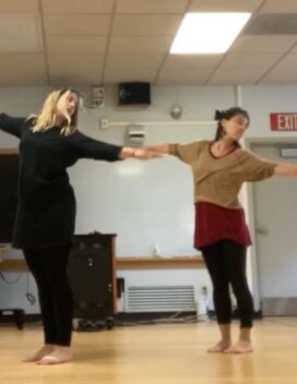 Two dancers stand side by side with arms extended