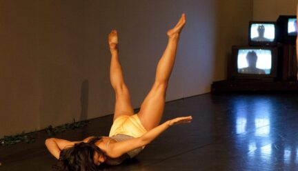 A dancers does a flip with her legs behind her
