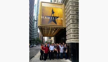 Lighting students in front of Hamilton marquee