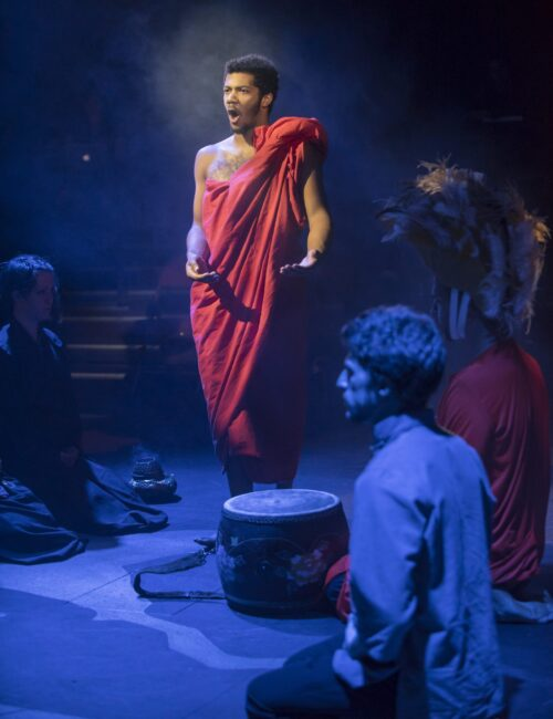 Person in toga standing in shaft of light during theatre production
