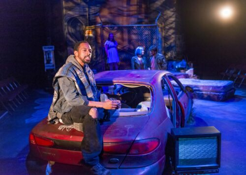 Young person sitting on trunk of car in Studio Theatre production