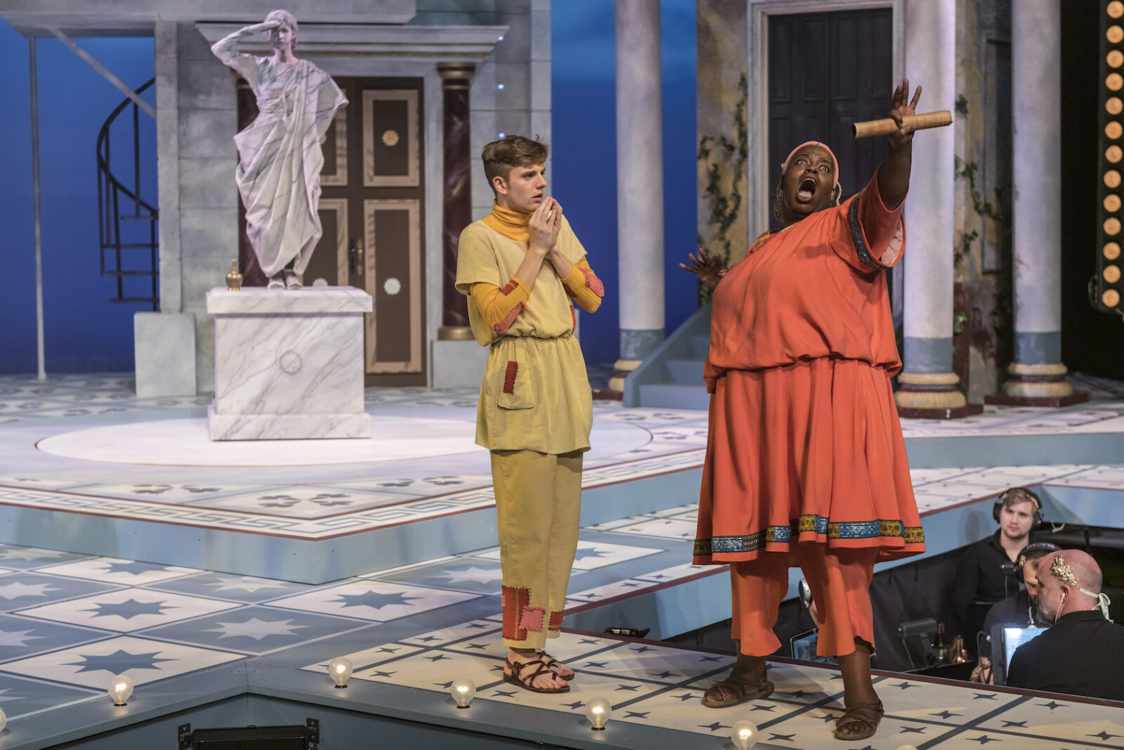 Two actors engage onstage in Roman costumes. One gestures toward the audience.